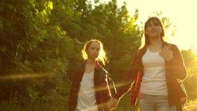 Κορίτσι οδοιπόρων τα κορίτσια εφήβων ταξιδεύουν και κρατούν τα χέρια ταξιδιώτες παιδιών τα κορίτσια με τα σακίδια πλάτης είναι στ απόθεμα βίντεο