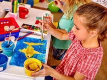 Κορίτσι ομάδας με τη ζωγραφική βουρτσών στον παιδικό σταθμό Στοκ Εικόνες