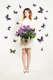 Κορίτσι ομορφιάς με τα λουλούδια και πεταλούδα στοκ εικόνα
