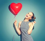 Κορίτσι ομορφιάς με το κόκκινο διαμορφωμένο καρδιά μπαλόνι αέρα Στοκ Φωτογραφίες