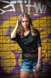 Κορίτσι ομορφιάς που θέτει τη μόδα κοντά στον τούβλινο τοίχο στην οδό Στοκ Εικόνες