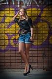 Κορίτσι ομορφιάς που θέτει τη μόδα κοντά στον τούβλινο τοίχο στην οδό Στοκ Φωτογραφία