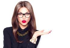 Κορίτσι ομορφιάς που φορά τα γυαλιά που παρουσιάζουν κενό copyspace Στοκ φωτογραφία με δικαίωμα ελεύθερης χρήσης
