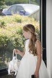 Κορίτσι λουλουδιών που κοιτάζει σε ένα παράθυρο Στοκ Εικόνες