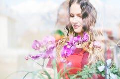 Κορίτσι λουλουδιών στο κατάστημά της λουλουδιών και εγκαταστάσεων Στοκ Εικόνες