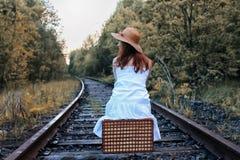 Κορίτσι πάρκων φθινοπώρου στα άσπρα sundress και ένα ψάθινο περπάτημα βαλιτσών Στοκ Εικόνες