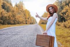 Κορίτσι πάρκων φθινοπώρου στα άσπρα sundress και ένα ψάθινο περπάτημα βαλιτσών Στοκ φωτογραφίες με δικαίωμα ελεύθερης χρήσης