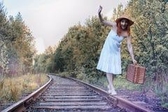 Κορίτσι πάρκων φθινοπώρου στα άσπρα sundress και ένα ψάθινο περπάτημα βαλιτσών Στοκ εικόνες με δικαίωμα ελεύθερης χρήσης