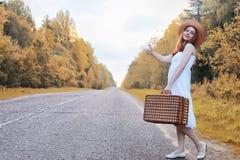 Κορίτσι πάρκων φθινοπώρου στα άσπρα sundress και ένα ψάθινο περπάτημα βαλιτσών Στοκ φωτογραφία με δικαίωμα ελεύθερης χρήσης