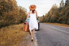 Κορίτσι πάρκων φθινοπώρου στα άσπρα sundress και ένα ψάθινο περπάτημα βαλιτσών Στοκ εικόνα με δικαίωμα ελεύθερης χρήσης