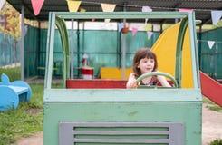 Κορίτσι πέντε έτη διασκέδασης που απεικονίζει τον οδηγό ενός ξύλινου αυτοκινήτου στην παιδική χαρά στοκ φωτογραφία
