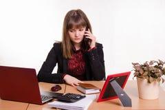 Κορίτσι πίσω από το γραφείο γραφείων στο τηλέφωνο που ακούει έναν φίλο Στοκ φωτογραφία με δικαίωμα ελεύθερης χρήσης