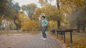 Κορίτσι παίζει στο φθινοπωρινό πάρκο Παιδιά που πετούν κίτρινα και κόκκινα φύλλα Μωρό με βελανιδιά και φύλλα σφενδάμνου Φυλλώματα απόθεμα βίντεο
