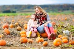 Κορίτσι παιδάκι και όμορφη μητέρα που έχουν τη διασκέδαση με την καλλιέργεια σε ένα μπάλωμα κολοκύθας Παραδοσιακό οικογενειακό φε στοκ εικόνες με δικαίωμα ελεύθερης χρήσης