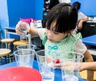 Κορίτσι παιδικών σταθμών που χύνει τη σαφή λύση σε ένα φλυτζάνι στο μπλε tabl Στοκ Εικόνα