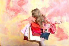 Κορίτσι παιδιών με το παρόν πακέτο στο ζωηρόχρωμο υπόβαθρο στοκ φωτογραφία