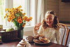 Κορίτσι παιδιών που έχει το πρόγευμα στο σπίτι το πρωί φθινοπώρου Πραγματικό άνετο σύγχρονο εσωτερικό στο εξοχικό σπίτι Στοκ Φωτογραφία