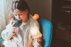 Κορίτσι παιδιών που πίνει το καυτό κακάο στο σπίτι στο χειμερινό Σαββατοκύριακο, που κάθεται στην άνετη καρέκλα στοκ φωτογραφίες με δικαίωμα ελεύθερης χρήσης