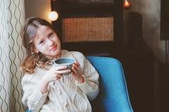 Κορίτσι παιδιών που πίνει το καυτό κακάο στο σπίτι στο χειμερινό Σαββατοκύριακο, που κάθεται στην άνετη καρέκλα στοκ εικόνες με δικαίωμα ελεύθερης χρήσης