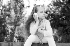 Κορίτσι παιδιών στην ονειροπόλο μουσική ακούσματος προσώπου υπαίθρια με τα ακουστικά, υπόβαθρο φύσης Το κορίτσι με μακρυμάλλη κάθ Στοκ Φωτογραφία
