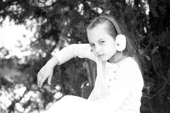 Κορίτσι παιδιών στην ονειροπόλο μουσική ακούσματος προσώπου υπαίθρια με τα ακουστικά, υπόβαθρο φύσης Το κορίτσι με μακρυμάλλη κάθ Στοκ εικόνα με δικαίωμα ελεύθερης χρήσης
