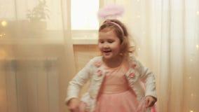Κορίτσι παιδιών στο κοστούμι αγγέλου ή νεράιδα που γελά και που χορεύει Έννοια της μαγικής και εκπλήρωσης επιθυμίας φιλμ μικρού μήκους