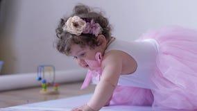 Κορίτσι παιδιών στο ρόδινο φόρεμα που σέρνεται στο άσπρο υπόβαθρο στο εσωτερικό στη σύνοδο φωτογραφιών φιλμ μικρού μήκους