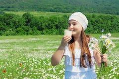 Κορίτσι παιδιών με τα λουλούδια και το ποτήρι του γάλακτος Στοκ εικόνες με δικαίωμα ελεύθερης χρήσης