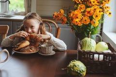 Κορίτσι παιδιών που έχει το πρόγευμα στο σπίτι το πρωί φθινοπώρου Πραγματικό άνετο σύγχρονο εσωτερικό στο εξοχικό σπίτι Στοκ φωτογραφίες με δικαίωμα ελεύθερης χρήσης