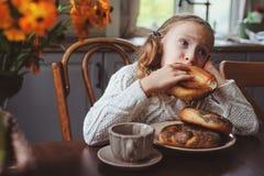 Κορίτσι παιδιών που έχει το πρόγευμα στο σπίτι το πρωί φθινοπώρου Πραγματικό άνετο σύγχρονο εσωτερικό στο εξοχικό σπίτι Στοκ φωτογραφία με δικαίωμα ελεύθερης χρήσης