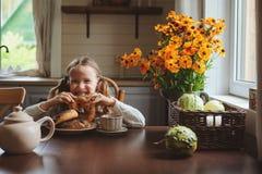 Κορίτσι παιδιών που έχει το πρόγευμα στο σπίτι το πρωί φθινοπώρου Πραγματικό άνετο σύγχρονο εσωτερικό στο εξοχικό σπίτι Στοκ Εικόνα