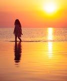 Κορίτσι παιδιών που περπατά στη θάλασσα ηλιοβασιλέματος στοκ φωτογραφίες με δικαίωμα ελεύθερης χρήσης
