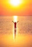 Κορίτσι παιδιών που περπατά στη θάλασσα ηλιοβασιλέματος στοκ εικόνα με δικαίωμα ελεύθερης χρήσης