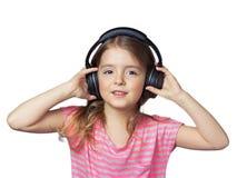 Κορίτσι παιδιών που χαμογελά στα ακουστικά που απομονώνονται στο λευκό Στοκ Φωτογραφία
