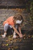 Κορίτσι παιδιών στην πορτοκαλιά ζακέτα που συλλέγει τα φύλλα στα παλαιά σκαλοπάτια πετρών Στοκ εικόνα με δικαίωμα ελεύθερης χρήσης