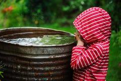 Κορίτσι παιδιών στο κόκκινο παιχνίδι αδιάβροχων με το βαρέλι νερού στο βροχερό θερινό κήπο Οικονομία νερού και προσοχή φύσης Στοκ Φωτογραφία