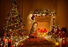 Κορίτσι παιδιών Χριστουγέννων που χαιρετά το παρόν κιβώτιο δώρων, παιδί στο δωμάτιο Χριστουγέννων Στοκ Φωτογραφίες