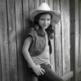 Κορίτσι παιδιών ως παιδί cowgirl που θέτει στον ξύλινο φράκτη στοκ εικόνα με δικαίωμα ελεύθερης χρήσης