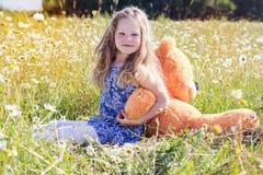 Κορίτσι παιδιών camomile στον τομέα με τη teddy αρκούδα Στοκ φωτογραφία με δικαίωμα ελεύθερης χρήσης