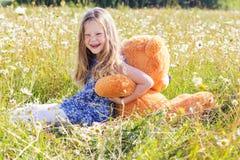 Κορίτσι παιδιών camomile στον τομέα με τη teddy αρκούδα Στοκ φωτογραφίες με δικαίωμα ελεύθερης χρήσης