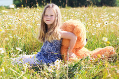 Κορίτσι παιδιών camomile στον τομέα με τη teddy αρκούδα Στοκ Εικόνες