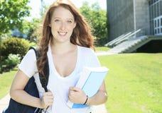 Κορίτσι πανεπιστημίου/φοιτητών πανεπιστημίου που φαίνεται ευτυχές στοκ εικόνες