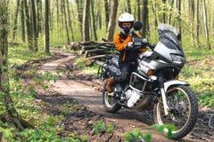 Κορίτσι ποδηλατών που φορά μια εξάρτηση μοτοσικλετών, προστατευτική ενδυμασία, εξοπλισμός, τουριστική μοτοσικλέτα περιπέτειας με  στοκ εικόνες με δικαίωμα ελεύθερης χρήσης
