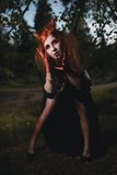 Κορίτσι πορτρέτου με την κόκκινη τρίχα και αιματηρό βαμπίρ προσώπου, δολοφόνος, ψυχο, θέμα αποκριών, αιματηρή γυναίκα Στοκ εικόνες με δικαίωμα ελεύθερης χρήσης
