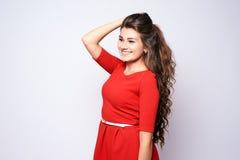 Κορίτσι πορτρέτου όμορφο brunette Κόκκινο φόρεμα Άσπρη ανασκόπηση Στοκ Εικόνες