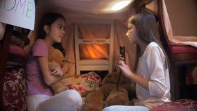 Κορίτσι που λέει τη τρομακτική ιστορία στην αδελφή της στη σκηνή σκηνών ερυθρόδερμων selfmade τη νύχτα απόθεμα βίντεο