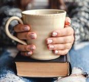 Κορίτσι που έχει ένα κενό με το φλυτζάνι του φρέσκου καφέ μετά από να διαβάσει τα βιβλία ή να μελετήσει στοκ φωτογραφία με δικαίωμα ελεύθερης χρήσης