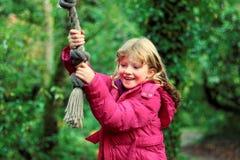 Κορίτσι που έχει τη διασκέδαση στην ταλάντευση σχοινιών δέντρων στοκ εικόνες