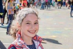 Κορίτσι που έχει τη διασκέδαση στο φεστιβάλ των χρωμάτων Στοκ Εικόνα