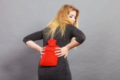 Κορίτσι που έχει τον πόνο στην πλάτη, που κρατά το μπουκάλι ζεστού νερού Στοκ Φωτογραφίες